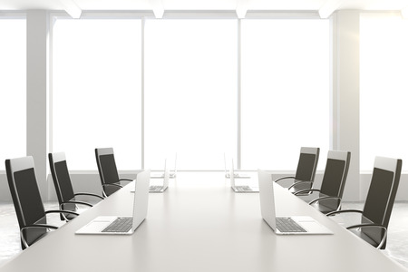 Empty conference table with a laptop and chairs and a large window