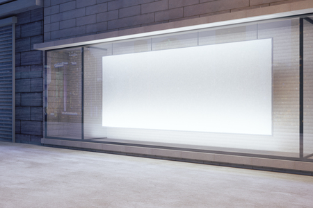 shop interior: Large blank banner in a shop window at night, mock up Stock Photo
