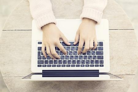 cenital: Mujer escribiendo en un ordenador portátil en la mesa de madera al aire libre