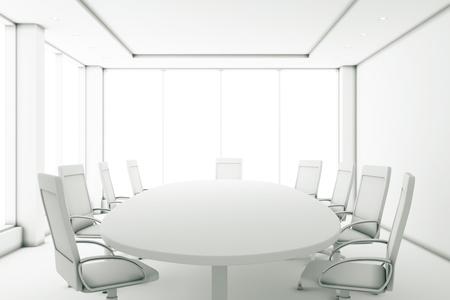 Całkowicie biała sala konferencyjna przy okrągłym stole i dużymi oknami