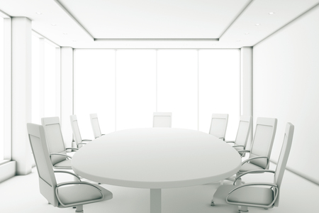 Completely white meeting room with a round table and large windows