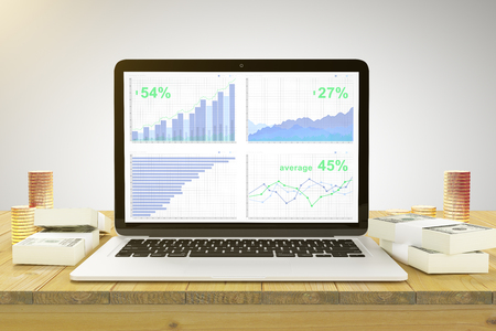 pc screen: Business chart on laptop screen on wooden table with gold coins and stacks of money Stock Photo