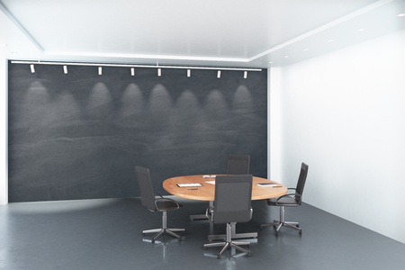round chairs: Round wooden table with chairs with blank big blackboard in conference room
