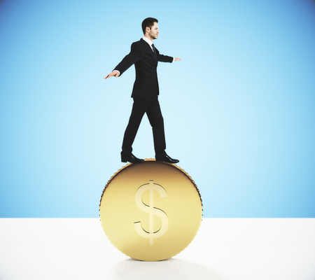 balances: Currency exchange concept with businessman balances on big gold dollar coin Stock Photo