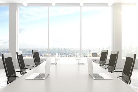 Moderne Konferenzraum mit Möbeln, Laptops, großen Fenstern und Blick auf die Stadt