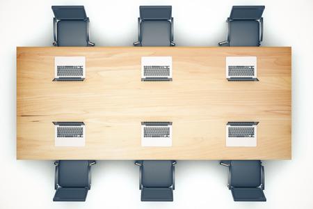 reuniones empresariales: Vista desde arriba de la mesa de reuniones de madera con sillas y un ordenador portátil