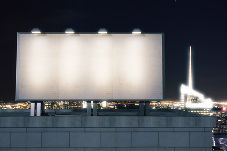 Big empty billboard on the background of the city at night, mock up 写真素材