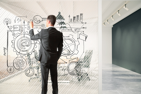 Man draws business plan on a glass partition in the meeting room, business concept
