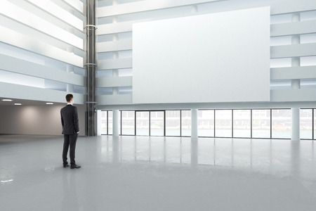man looking at a blank white banner in a large bright hall, mock up