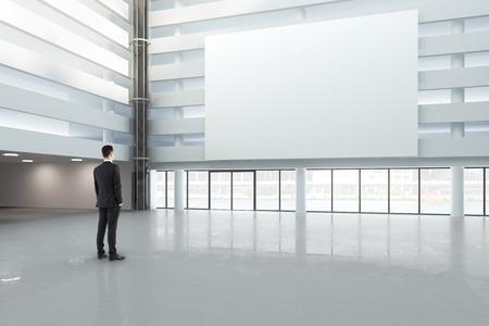 man op zoek naar een lege witte banner in een grote lichte hal, mock-up