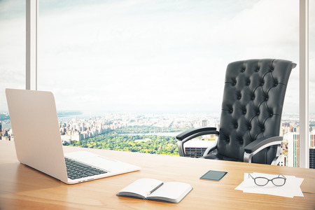 Modern work place with wooden table, laptop and classic leather chair at city background