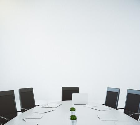 ノート パソコンと白い壁の背景に椅子と大きな白い楕円形テーブル