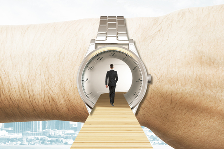 Time travel concept with businessman walking into the watches on the hand Standard-Bild