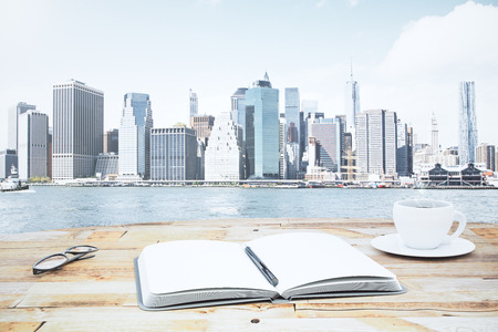 diary: Blank open diary with cup of coffee and eyeglasses on wooden table in front of financial district