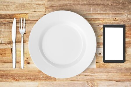 food absorption: White plate, blank smartphone screen, fork and knife on wooden table, mock up Stock Photo