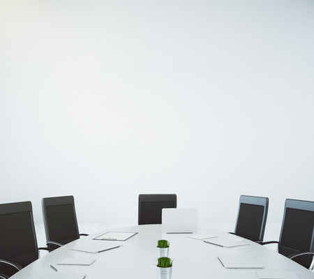 Big white oval table with laptop and chairs at white wall background Foto de archivo