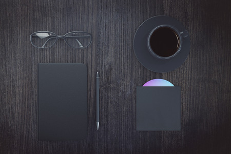 diary cover: Blank black diary cover with cup of coffee, eyeglasses and CD disk on wooden table, mock up Stock Photo