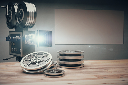 Cámara de película de la vendimia con las cintas de estilo antiguo y la película sobre la mesa de madera