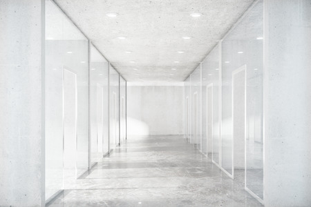 Long corridor with concrete floor and transparent walls in modern space