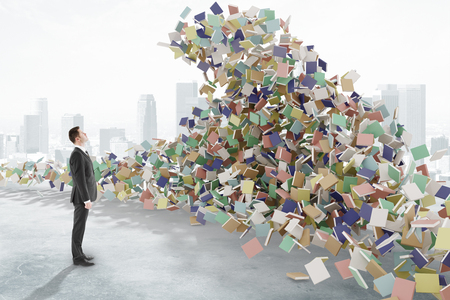Man looks at the tsunami waves consisting of books, education concept