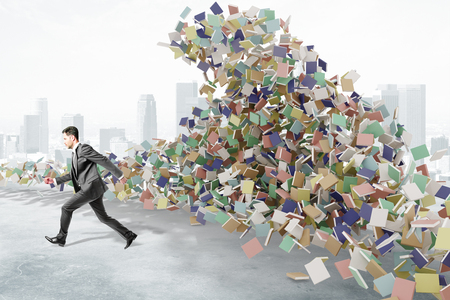 chaos: Education concept with businessman runs from the mountain of books at city background