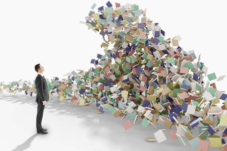 Education concept with businessman looks at the mountain of books