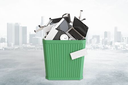 overwork: Big green trash busket with office accessories at city background