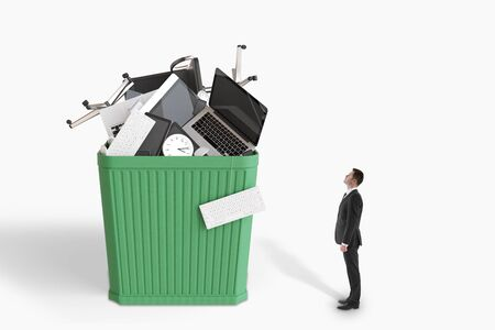 Businessman looks at huge green wastebusket with office accessories