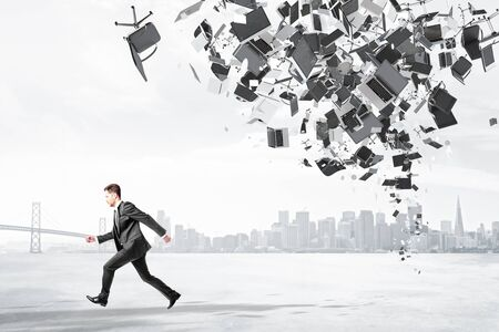 bureaucracy: Businessman runs from office garbage heap at city background Stock Photo