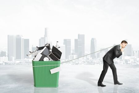 wastebasket: Businessman pulls the rope wastebasket with office accessoiries at city background