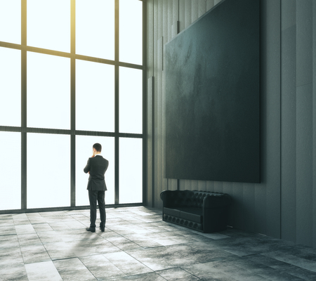 big picture: Businessman in loft room with blank black big picture, leather sofa and big window, mock up, 3D Render