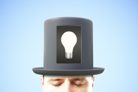 business mind: Idea concept with man in black cylinder and glowing light bulb in the center