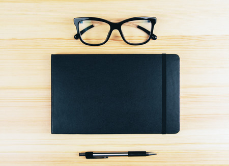 diary cover: Blank diary cover with eyeglasses and pen on wooden table Stock Photo