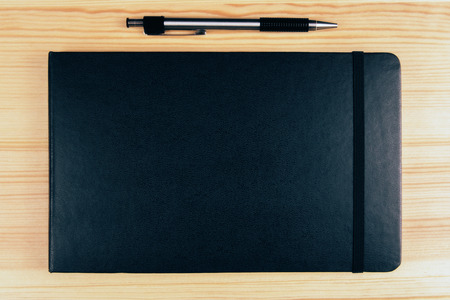 diary cover: Blank black diary cover and pen on wooden table, mock up