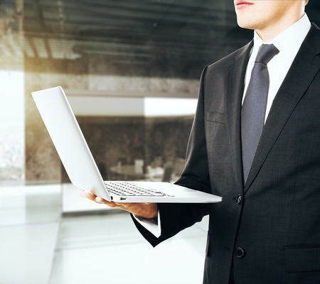 one hand: Businessman with opened laptop in one hand Stock Photo