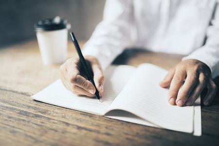 hombre escribiendo: Escritura del hombre en el espacio en blanco de papel de diario y la taza de café en la mesa de madera Foto de archivo
