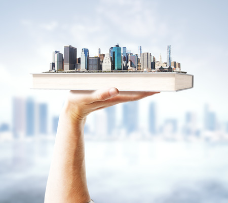 Hand holding book with city on blurry background. 3D Render