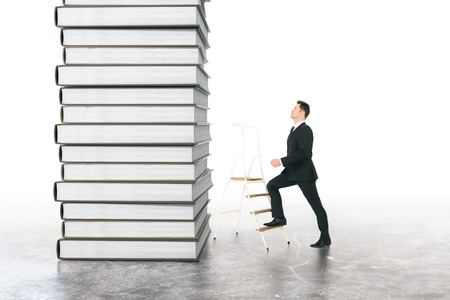 Education concept with businessman climbing book stack on concrete background Stock Photo