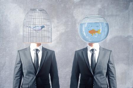 fishtank: Birdcage and fishtank headed businessmen on concrete background