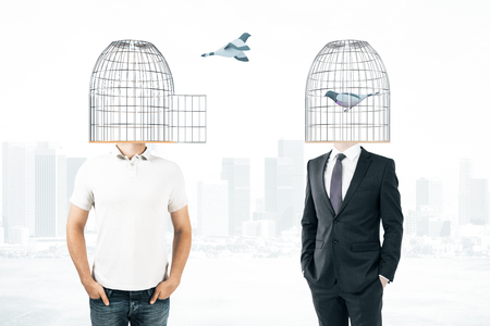 Businessperson and casual man with birdcages instead of heads Stock Photo