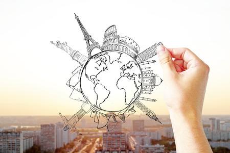globe terrestre dessin: Voyager notion avec la main mâle dessin globe avec vues sur fond ensoleillé ville