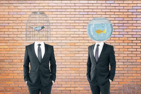 fishtank: Birdcage and fishtank headed businessmen on brick background Stock Photo