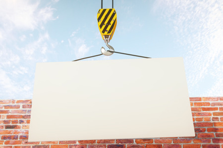 hook up: Blank banner on crane hook with clear sky and brick wall in the background. Mock up, 3D Rendering Stock Photo