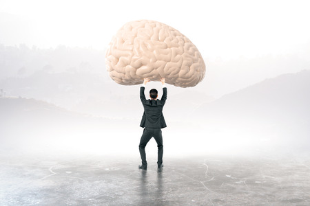 brainstem: Businessman holding brain with blurry landscape in the background
