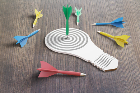 winning pitch: Goal concept with abstract lightbulb and colorful darts on dark wooden table. 3D Rendering