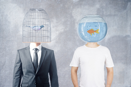 Businessman and casually dressed man with fishtank and birdcage instead of heads on concrete background