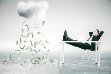 Concepto de crecimiento financiero con el empresario sentado en la mesa con los pies en alto y mirando a la lluvia de dinero abstracto. Representación 3D Foto de archivo - 55888580