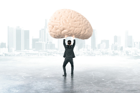 brainstem: Businessman holding brain with foggy city in the background