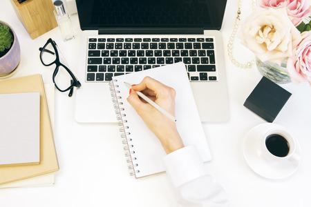 Topview der weiblichen Hand schriftlich in Notizblock auf weißem Desktop mit Notebook, Blumen, Parfüm und andere Sachen Standard-Bild - 55888601