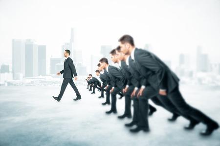 実行しようとして多くのビジネスマンと霧の街の背景にそれらの前を歩いて一つ競争概念